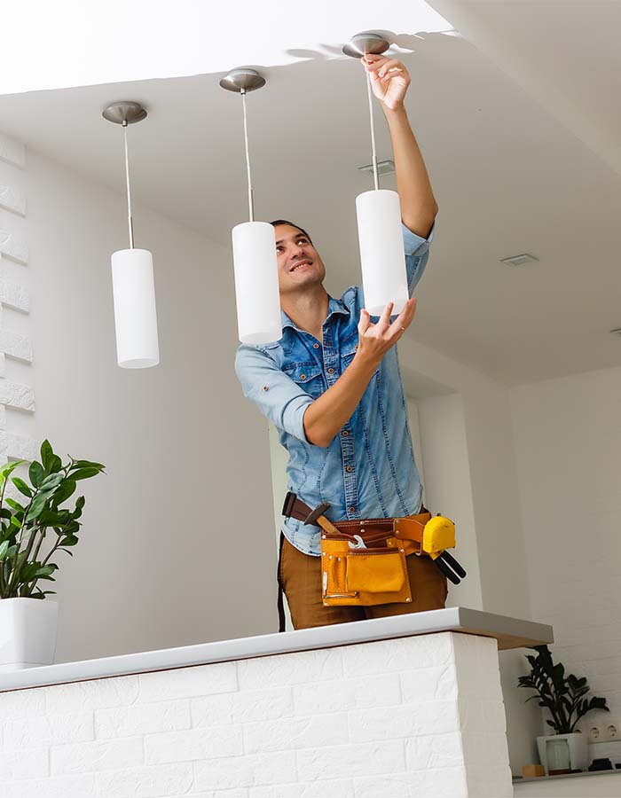 an electrician installing light fixtures; electric services