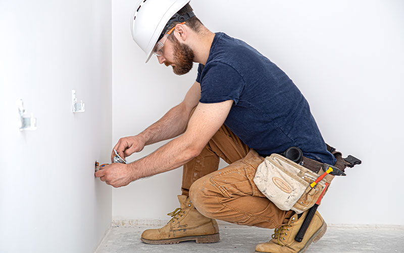 A residential electrician working on an outlet; he is crouched over the outlet wearing a blue shirt and hard hat